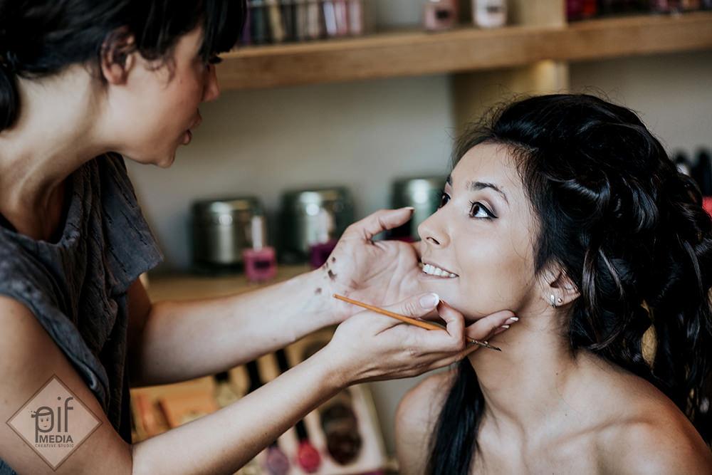 artistul make-up tine fata miresei in maini