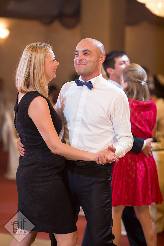 barbat cu papion albastru danseaza cu o fata blonda in rochie neagra la nunta mirilor