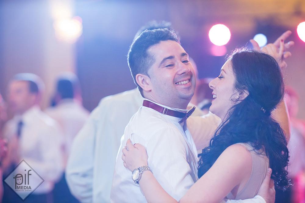 barbat cu papion visiniu danseaza cu o fata bruneta la nunta