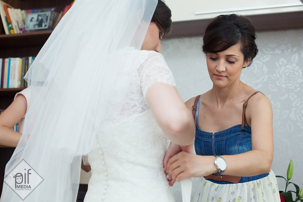 carmen cu spatele sora sa ii aranjeaza rochia de mireasa in fata