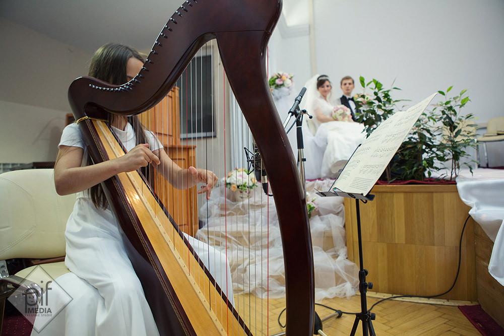 copil canta la harpa in biserica