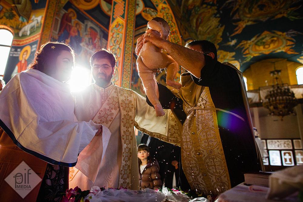 copilul dupa botez ridicat de preot si pus in bratele nasei