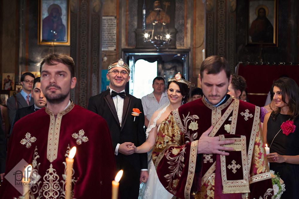 doi preoti tineri in fata iar in spate mirele si mireasa zambesc cu coroanele puse pe cap