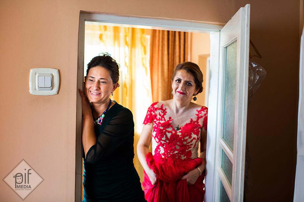 doua femei stau in usa si o privesc pe mireasa
