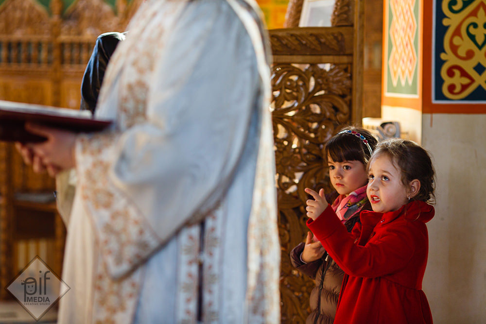 doua fetite in spatele preotului in biserica