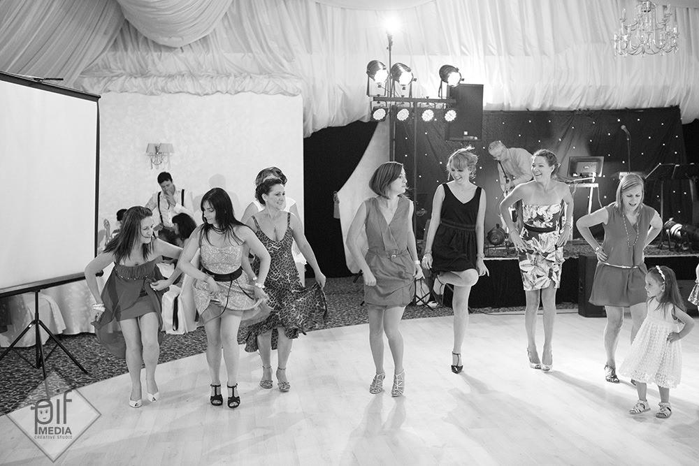 fetele danseaza la nunta aliniate iar in dreapta o fetita danseaza alaturi