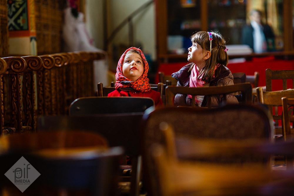 fetitele stau pe banca in biserica si privesc icoanele