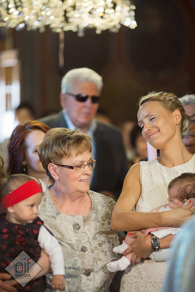 fiica nasei tine fetita in brate la botezul din biserica