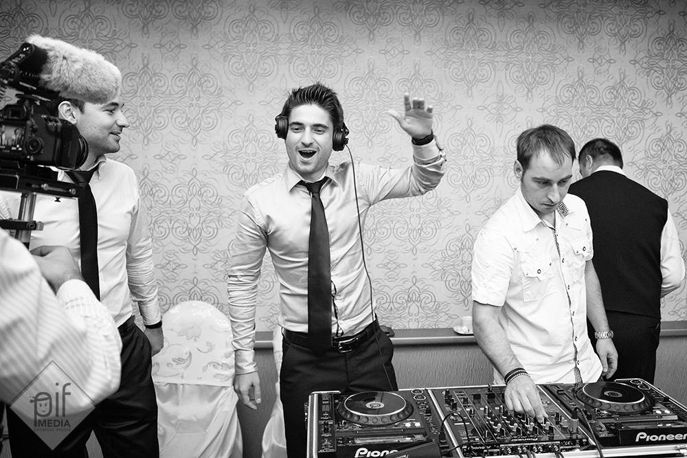 invitatii la pupitrul de dj mixeaza si pun muzica in fotografie se vede si cameramanul de la nunta