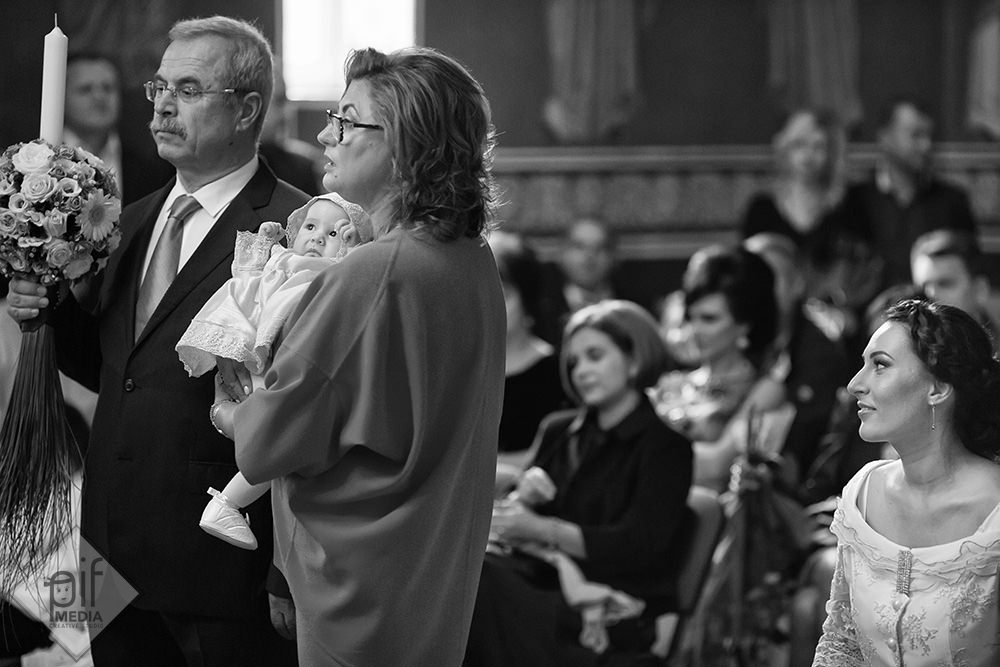 mama se uita la nasa care tine copilul in brate in fata altarului