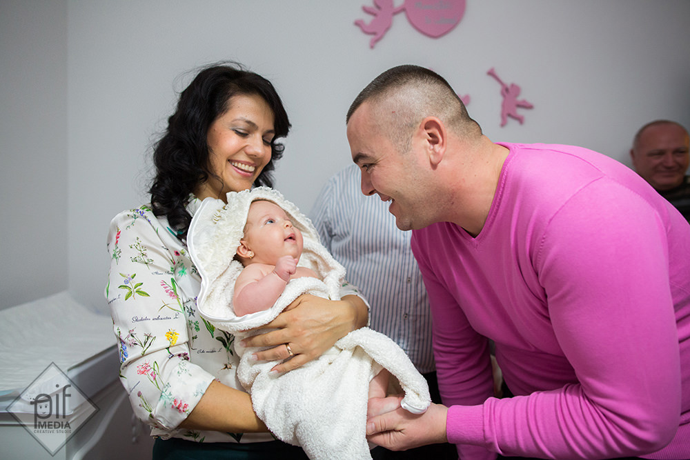 marian tatal imbracat in tricou roz isi priveste fiica care e in bratele nasei