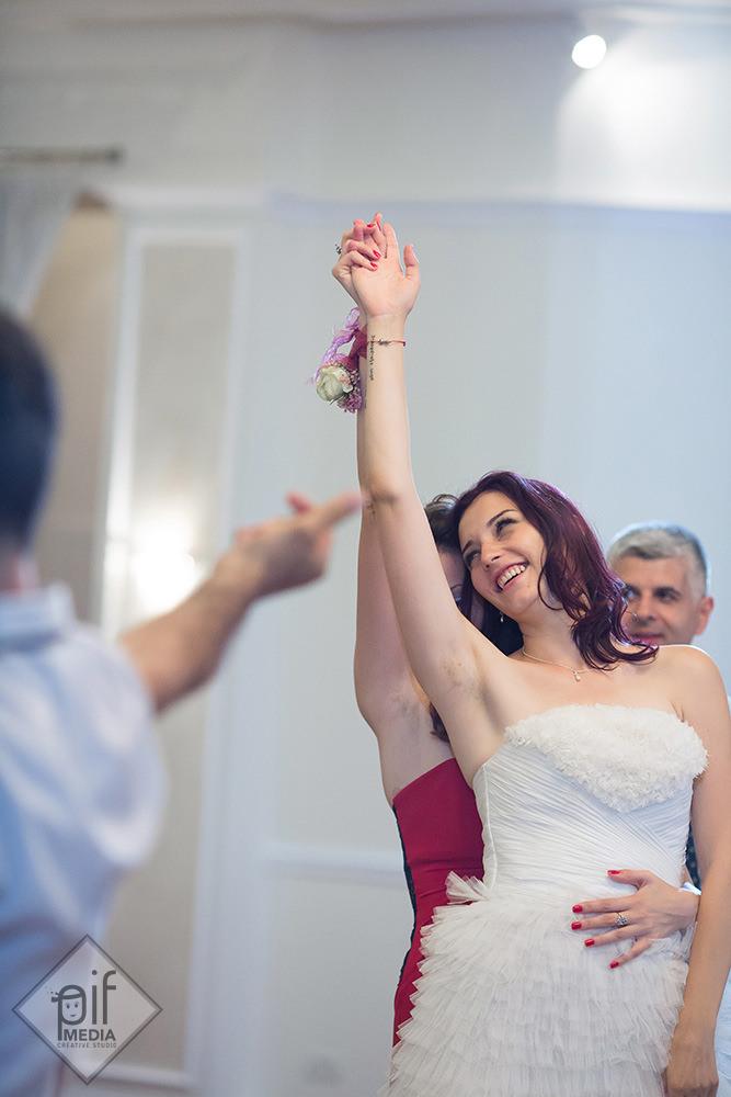 mireasa cu o mana ridicata in aer danseaza la nunta