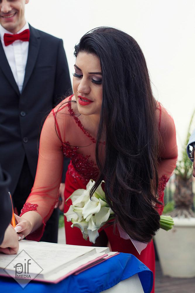 mireasa in rochie rosie semneaza certificatul de casatorie