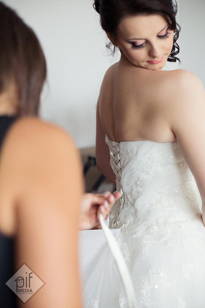 mireasa priveste in timp ce fetele ii leaga rochia cu snurul