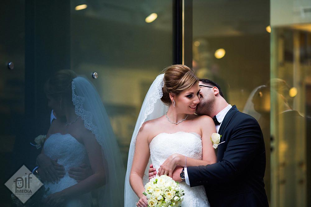 mirele imbratiseaza mireasa si o saruta pe gat langa un geam mare din sticla
