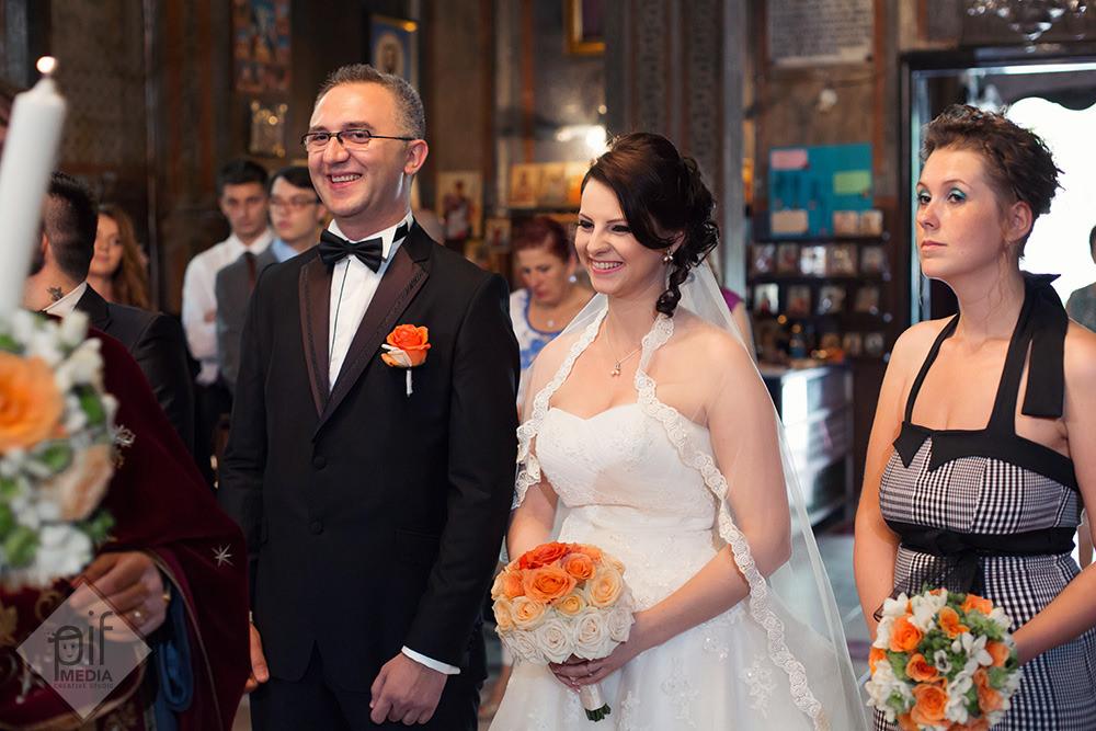 mirele si mireasa zambesc in biserica in timpul slujbei de casatorie