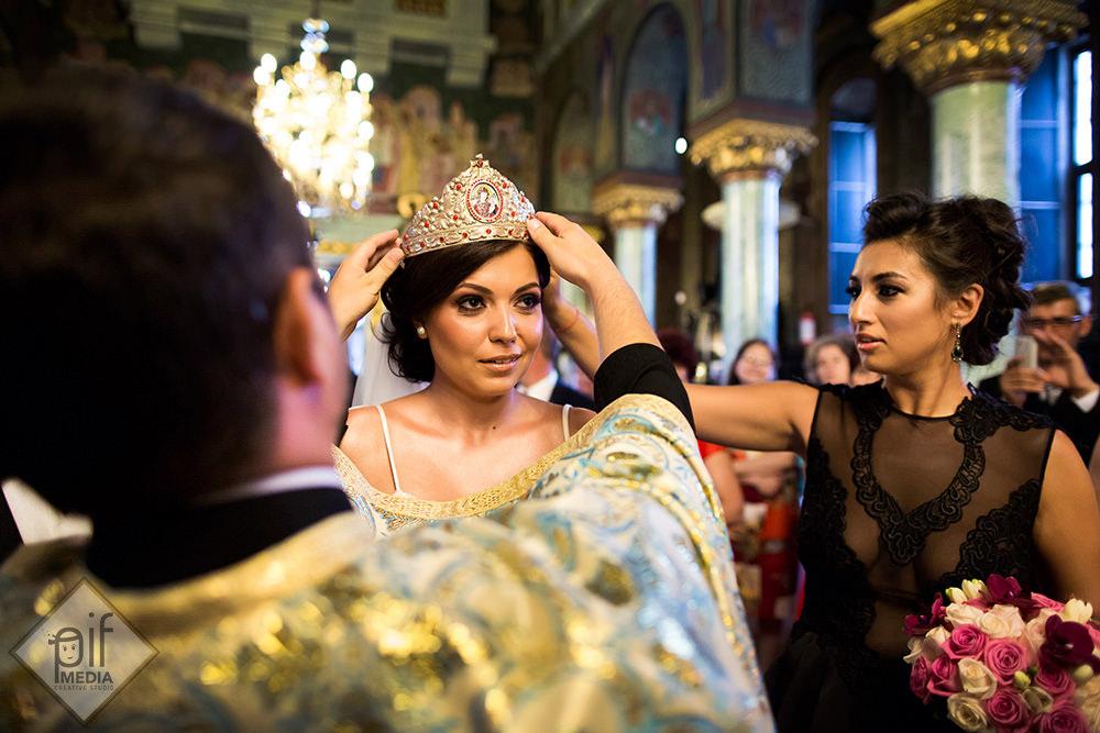 miresei i se pune coroana de catre preot iar nasa tine de ea
