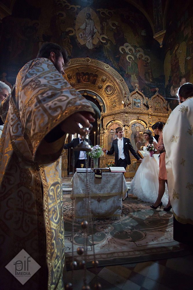 mirii alaturi de preoti si nasi inconjoara masa in biserica rusa