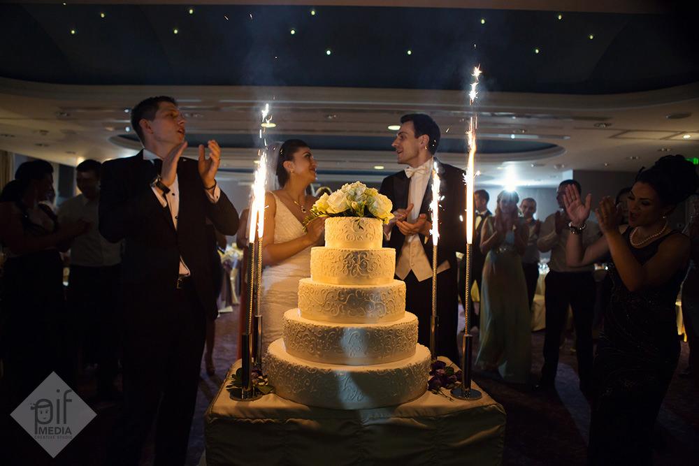 mirii langa tortul de nunta cu flori in varf