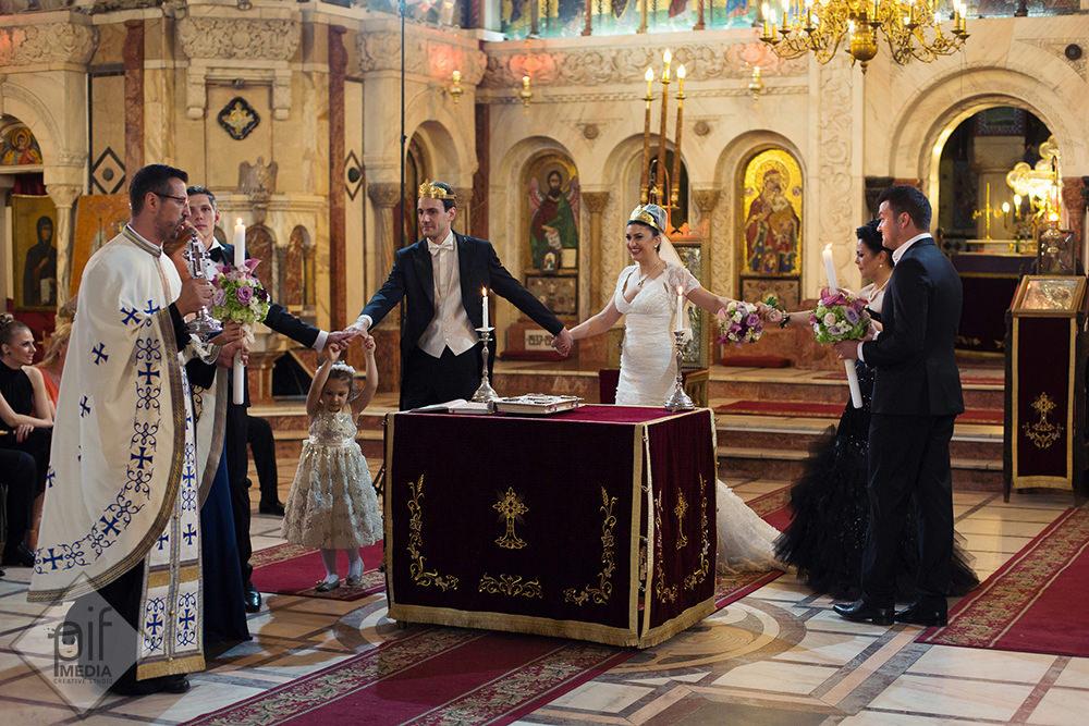 mirii preotul si o fetita inconjoara masa din biserica