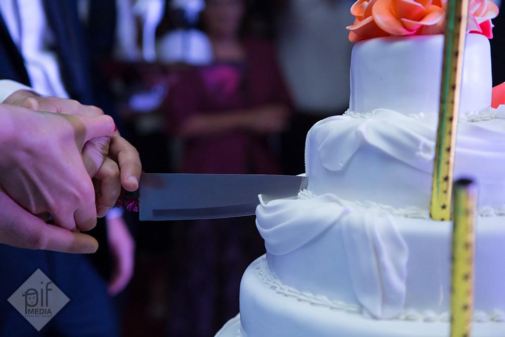 mirii si nasii cu mana pe cutit taie tortul cu flori rosii de la nunta