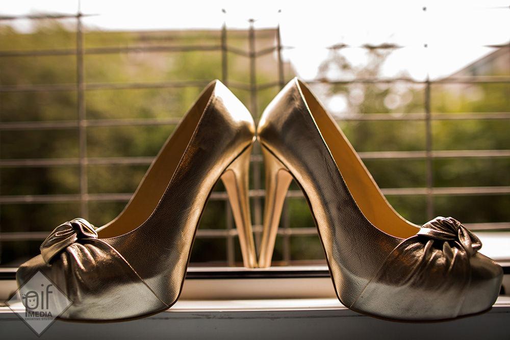 pantofii aurii ai miresei asezati langa geam