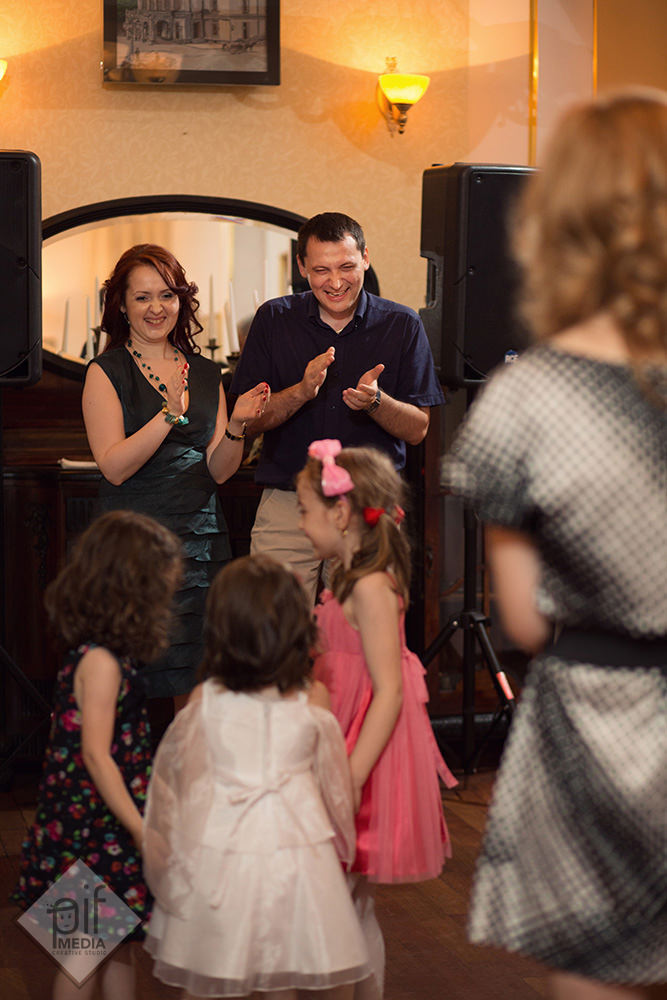 parintii fetitei aplauda in timp ce danseaza la locanta jaristea