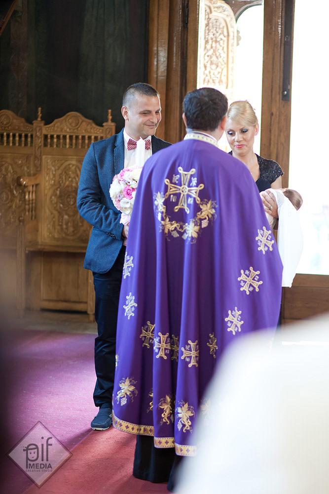 preot imbracat in haine mov in fata nasilor si a antoniei