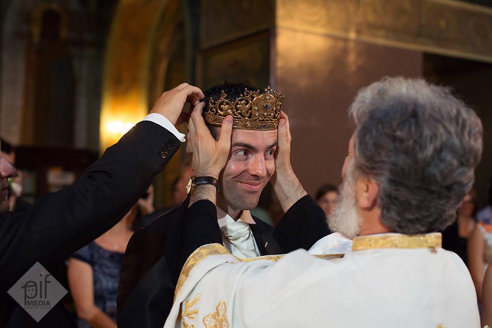 preotul aranjeaza coroana pe capul mirelui in biserica rusa