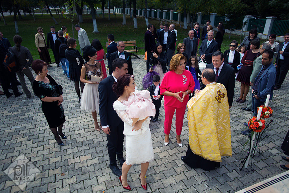 preotul ii intampina pe parinti si copil inainte de botez