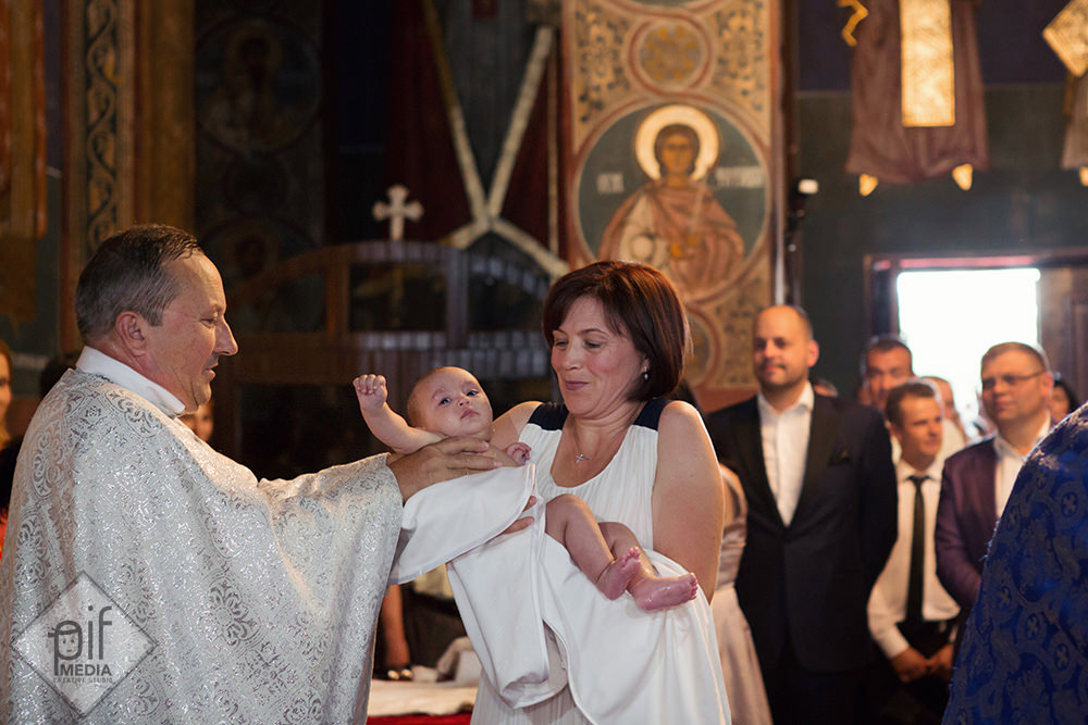 preotul o da pe micuta botezata in bratele nasei