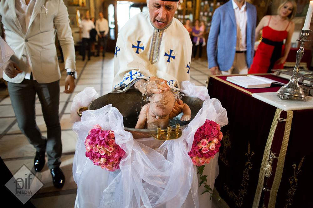 preotul scufunda copilul in cristelnita si ii pune apa pe cap