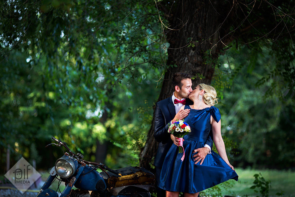 se saruta mirii langa un copac si o motocicleta
