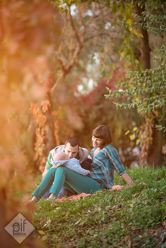 tatal se uita duios la copil parintii stau intinsi pe patura in iarba