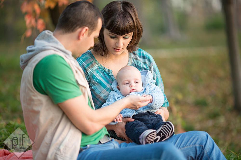 tatal si mama imbracat in haine colorate il tin pe bebe in brate pe patura in parc