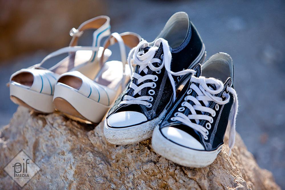 tenisi mire si pantofi mireasa pe o piatra la malul marii