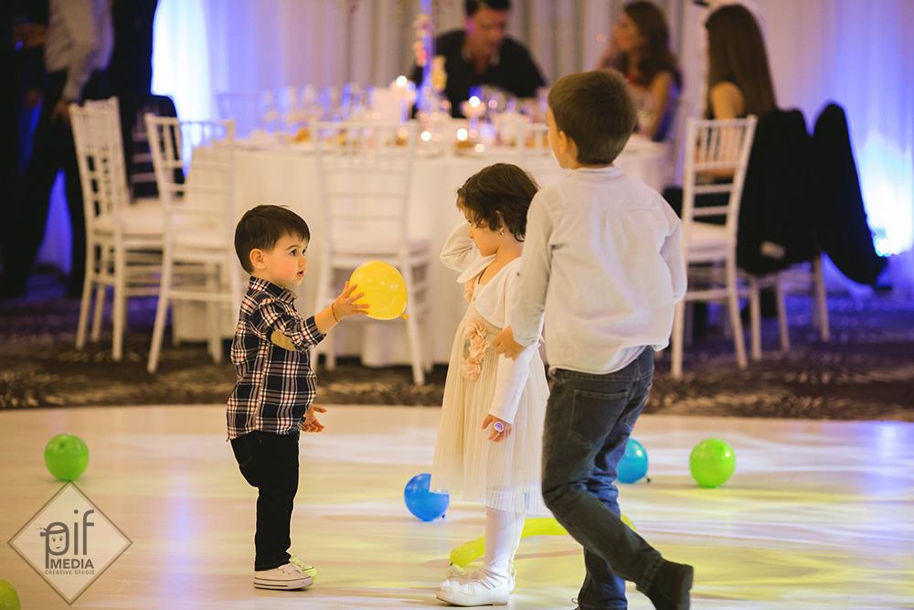 trei copii de la botez se joaca cu bile