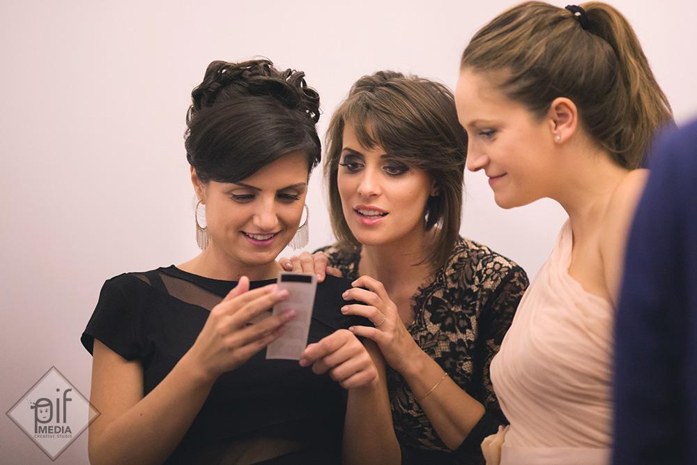 trei fete invitate la botez se uita la un telefon