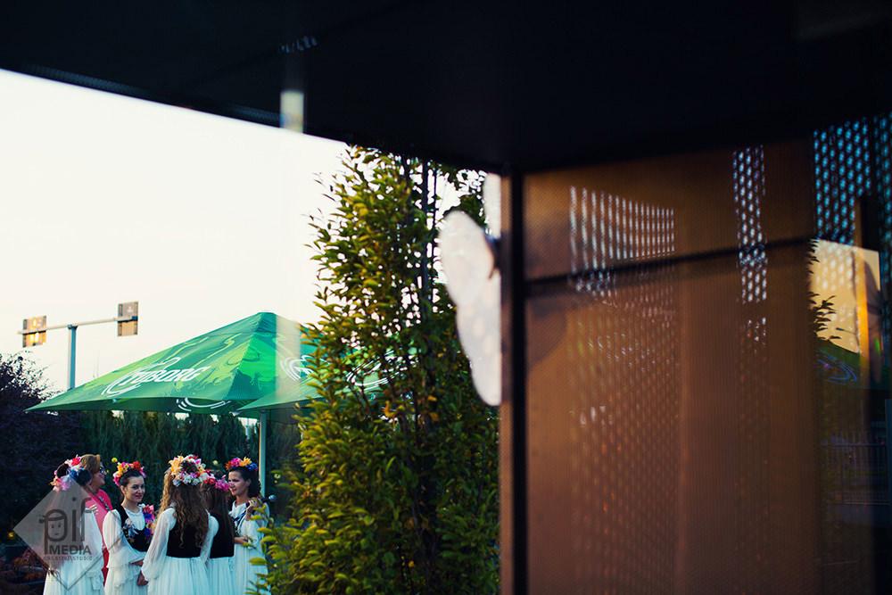 ursitoarele zurli in fata restaurantului langa o umbrela verde